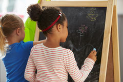 Two Girls Drawing Picture On Blackboard At Home Stock Photography
