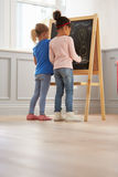 Two Girls Drawing Picture On Blackboard At Home Royalty Free Stock Photos
