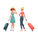 Two girls, in dress and jeans, travelling together with suitcases Stock Images