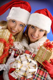 Two Girls Dressed as Santa Claus Rejoice With Christmas Presents Royalty Free Stock Image