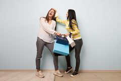 Two girls dressed in nice casual clothes fight and take each other shopping bags on the white background stock photos