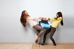 Two girls dressed in nice casual clothes pull and take each other shopping bags on the white background stock photo