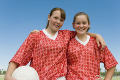 Two Girls Dressed To Play Football. Portrait of happy two young girls dressed to play football against clear sky Stock Images