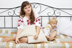 Two girls dressed in Ukrainian on the bed. Studio photography Royalty Free Stock Photo