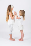 Two girls dressed in white playing Stock Image