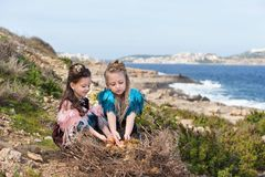 Two girls in dresses of birds with wings and feathers put in a nest eggs on the rock shore of the blue sea Stock Image