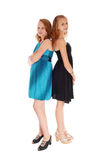 Two girls in dresses standing back to back. Two beautiful sisters in blue and black dresses standing back to back, in high heels, isolated for white background stock images