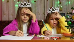 Two girls in dressing gowns sitting at a table and writing letter to Santa Claus. Two girls in dressing gowns sitting at a table and writing a letter to Santa stock video footage