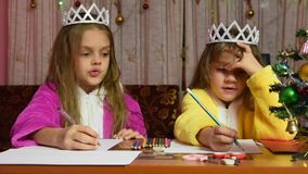 Two girls in dressing gowns sitting at a table and writing a letter to Santa Claus, one of them thinks funny stock video