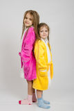 Two girls in dressing gowns stand back to back Stock Photo