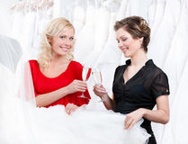Two girls drink champagne or wine. While discussing and choosing the wedding gown royalty free stock images