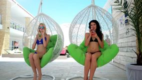 Two girls drink cocktails on armchairs. Azure, Ukraine - 15 July 2016: Two girls drink cocktails on armchairs in Azure 15 July 2016 beautiful young woman stock video footage