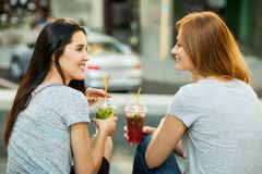 Two girls drink cold cocktails. Two girls talk and drink cold cocktails, pretty friends, nice girlfriends walk around the city and drink lemonade Royalty Free Stock Photo
