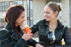 Two girls drink juice Stock Images