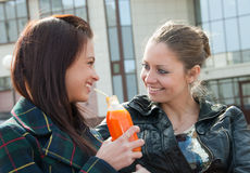 Two girls drink juice royalty free stock photography