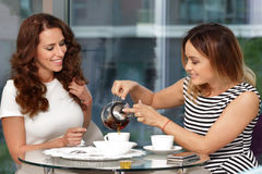 Two girls drink tea in cafe. And talking stock photography