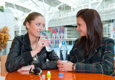 Two girls drink water in food court in a mall. Two young girls drink water in food court in a mall Stock Images