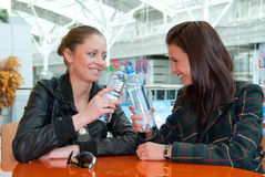 Two girls drink water in food court in a mall royalty free stock images
