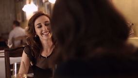 Two girls drink wine in restaurant and talking. Female friends women red-haired and brunette enjoying a glass of white wine in a small wine bar and socialize stock video footage