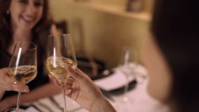 Two girls drink wine in restaurant and talking. Two friends women red-haired and brunette enjoying a glass of white wine in a small wine bar and socialize stock video footage