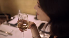 Two girls drink wine in restaurant and talking. Two friends women red-haired and brunette enjoying a glass of white wine in a small wine bar and socialize stock video