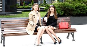 Two girls drinking coffe on a park bench. Two girls drinking coffe on the bench in front of business сentre stock footage