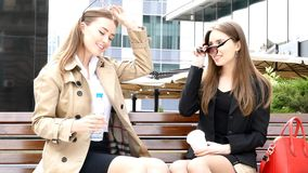 Two girls drinking coffe on a park bench. Two girls drinking coffe on the bench in front of business сentre stock video