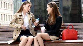 Two girls drinking coffe on a park bench. Two girls drinking coffe on the bench in front of business сentre stock video footage