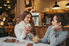 Two girls drinking coffee in cafe. Two best friends girls drinking coffee in cafe Royalty Free Stock Photos
