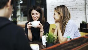 Two girls drinking coffee in a cafe with man sitting with his back to the camera. Blond woman drinking a beverage with a straw and her brunette friend are stock footage