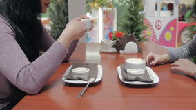 Two girls are drinking coffee and talking in a cafe. stock video