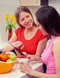 Girls drinking coffee and using tablet pc Stock Photography