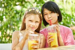 Two girls are drinking healthy orange juice. Two girls together drink healthy orange juice with the straw Stock Photos