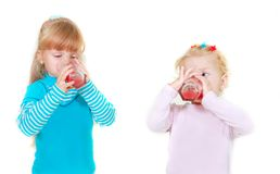 Two girls drinking juice Stock Photos