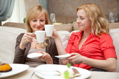 Two girls are drinking tea in cafe Stock Images