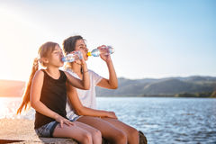 Two girls drinking water and sitting by the sea stock images