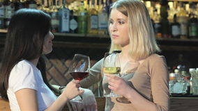 Two girls drinking wine at the bar. Two pretty looking women drinking wine at the bar. Blond caucasian girl drinkin white wine while asian girl drinking red wine stock video footage