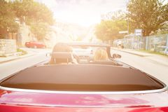Two girls driving convertible car. Back view of two girls driving red convertible car. Sun effect applied royalty free stock images