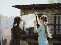 two girls dry clothes on the street. stock photo