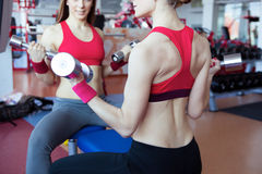 Two girls with dumbbell in fitness club Stock Photo