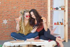 Two girls eat pizza in the room on the bed. make selfie on your smartphone. junk food. royalty free stock photography