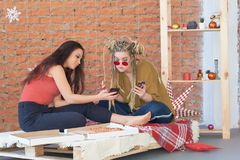 Two girls eat pizza in the room on the bed. make selfie on your smartphone. junk food. royalty free stock image