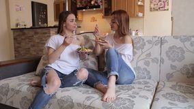 Two girls eat salad sitting on the couch. Two sexy girls in white t-shirts and ripped jeans eat vegetable salad and eggs sitting on the couch at home in front stock video footage