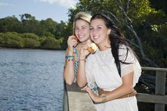 Two girls eating apples by the creek Stock Photo