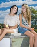 Two girls eating apples by the creek Royalty Free Stock Photos