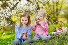 Two girls eating chocolate bunnies on Easter Royalty Free Stock Image