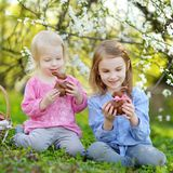 Two girls eating chocolate bunnies on Easter Royalty Free Stock Photo