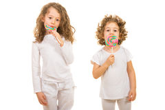 Two girls eating lollipops Stock Photos