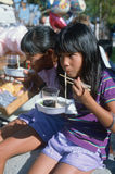 Two girls eating noodles Stock Photos