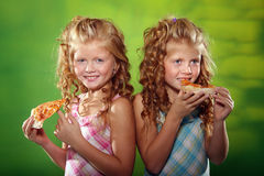 Two girls eating pizza. Two little girls eating pizza on the green background Royalty Free Stock Images